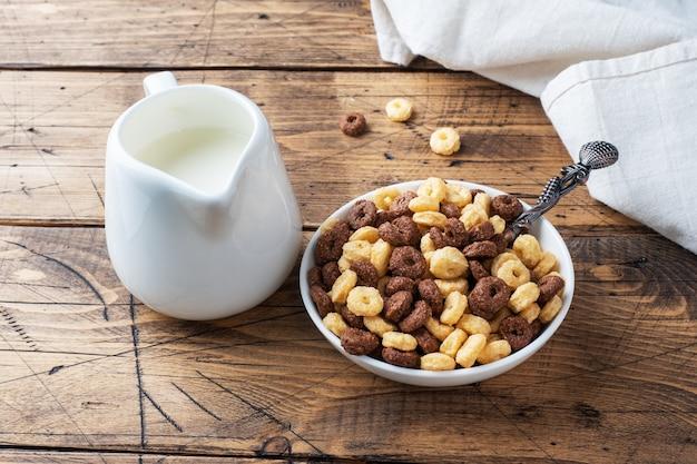 Droge ontbijtgranen. chocolade- en maïsringen gemaakt van natuurlijke granen met melk in een bord. houten rustieke achtergrond, kopieer ruimte.