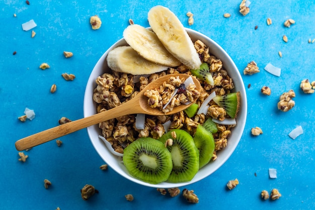 Droge ontbijtgranen. de knapperige kom van honingsmuesli met plakken van verse banaan en kiwi op een blauwe achtergrond. gezond, fitness en vezelvoeding. bovenaanzicht ontbijt tijd