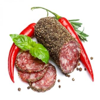 Droge organische salamiworst die met peper op geïsoleerd wit wordt behandeld