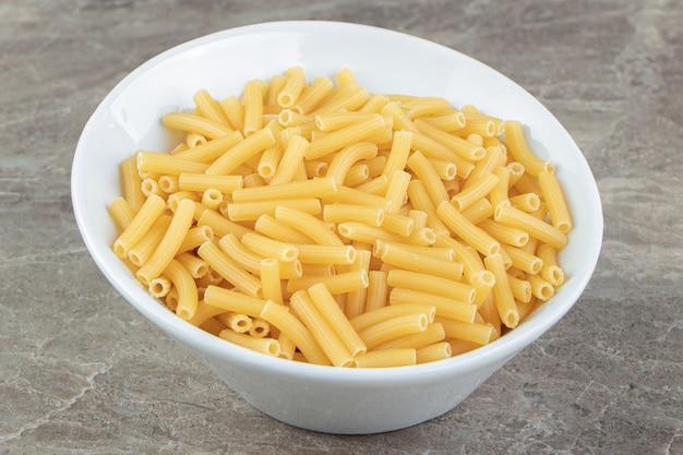 Droge pasta in de vorm van smalle buisjes in witte kom
