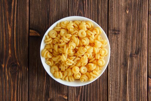 Droge pasta in een kom op een houten tafel. plat lag.