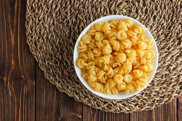 Droge pasta in een kom op houten en rieten placemat. plat lag.