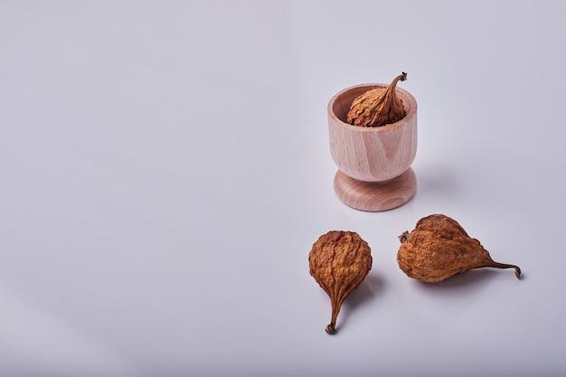 Droge peren in een houten beker en op de grijze achtergrond