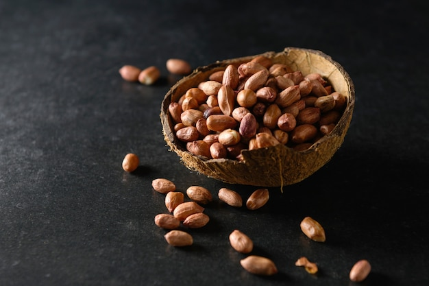 Droge pinda's in een kokosnootkom op een donkergrijze ondergrond