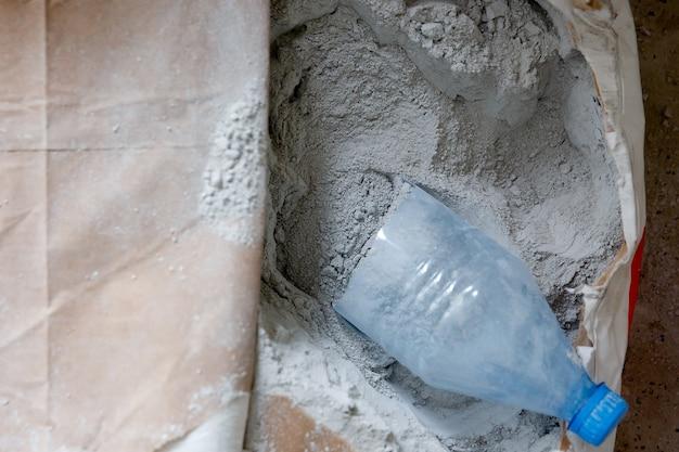 Droge poedergrijze mortel in een papieren zak