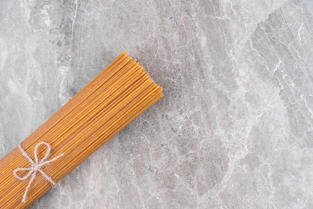 Droge rauwe spaghetti vastgebonden met touw op marmeren oppervlak.