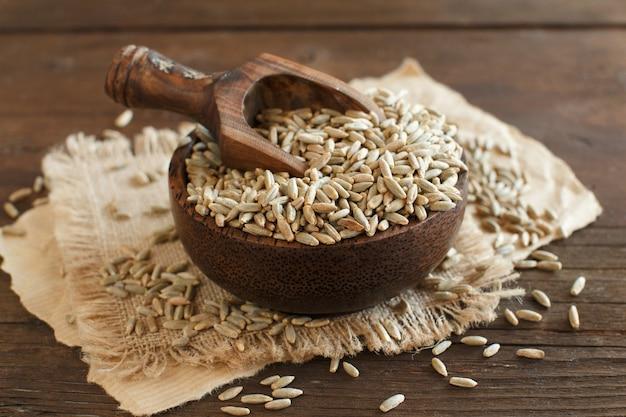 Droge raw rye grain in een kom met een lepel