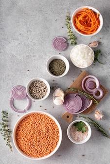 Droge rode linzen in een witte kom met uien en kruiden