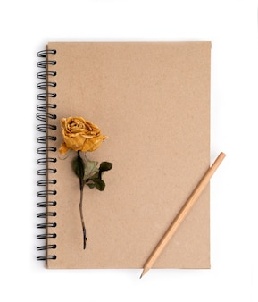 Droge roze bloem met potlood op notitieboekje