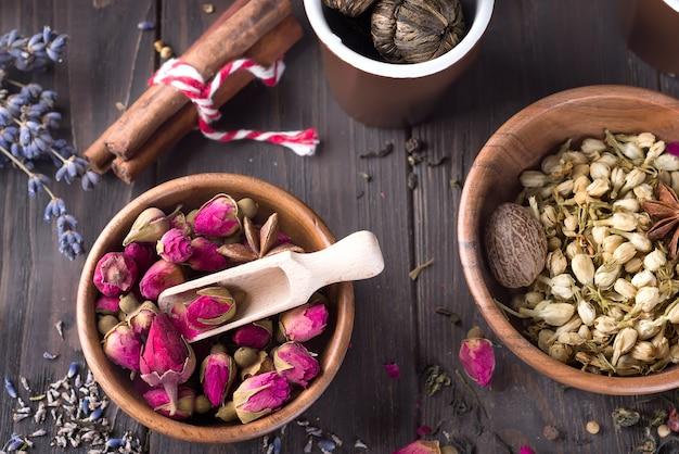 Droge roze knop in houten kom, die voor het maken van thee op houten achtergrond worden gebruikt.