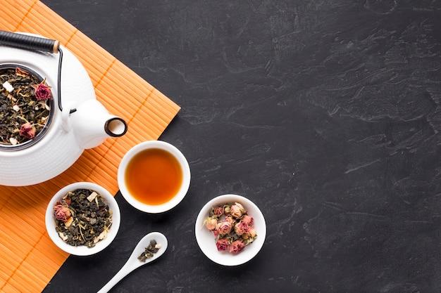 Droge rozen en theekruid met theepot op oranje placemat over zwarte stenen achtergrond