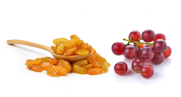 Droge rozijnen in de houten lepel en geïsoleerde druiven