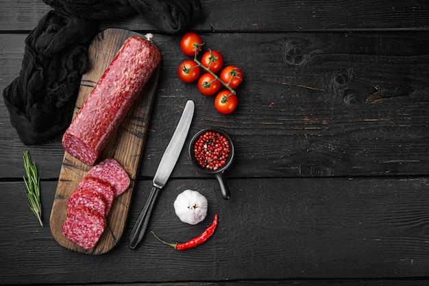 Droge salami worst met verse rozemarijn en kruiden set, op zwarte houten tafel, bovenaanzicht plat lag