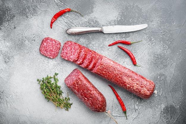 Droge salamiworst met verse rozemarijn en kruidenset, op grijze stenen tafelachtergrond, bovenaanzicht plat gelegd
