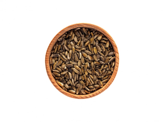 Droge silybum-zaden in een houten kop op een witte lijst