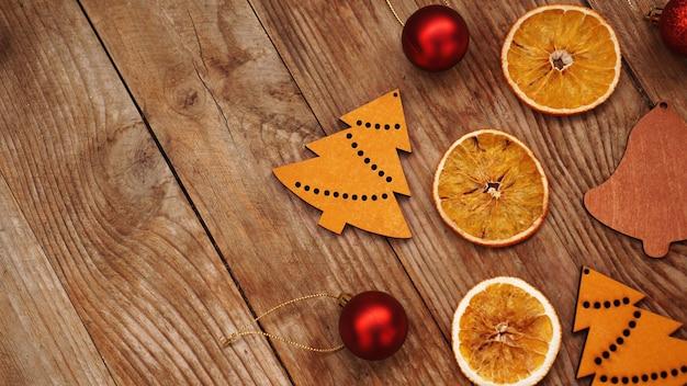 Droge sinaasappelen, rode ballen en houten kerstbeeldjes op rustieke bruine houten achtergrond met plaats voor tekst