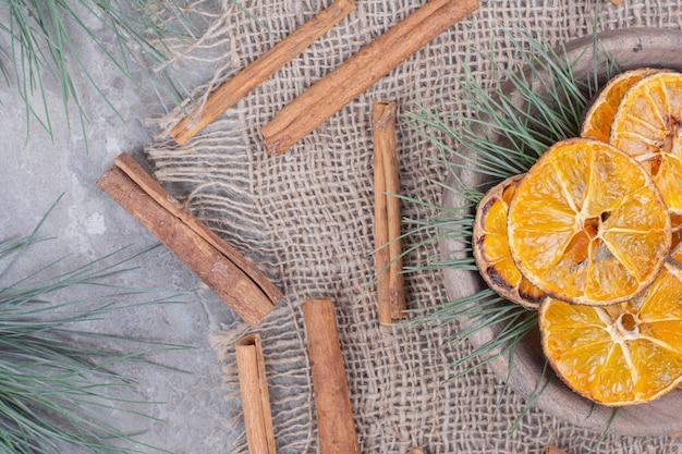Droge sinaasappelschijfjes in een kopje met eiken takken en kaneel