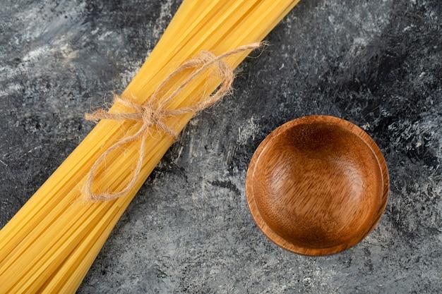 Droge spaghetti en houten kom op marmeren oppervlak