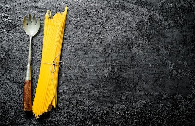 Droge spaghetti met pollepel op zwarte rustieke tafel.