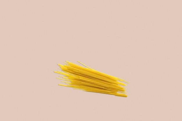 Droge spaghetti op een rode achtergrond voor het menu. geometrische achtergrond. plat leggen, ruimte kopiëren, bovenaanzicht.