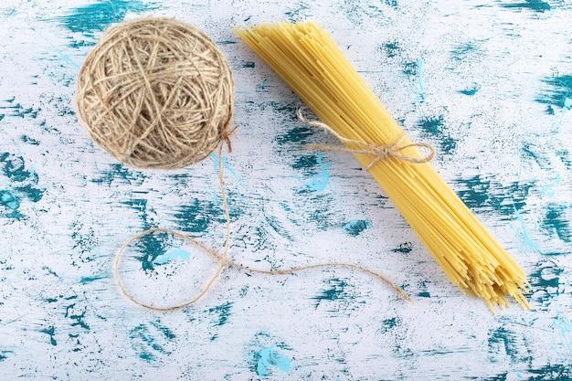 Droge spaghettideegwaren en garen op blauw.
