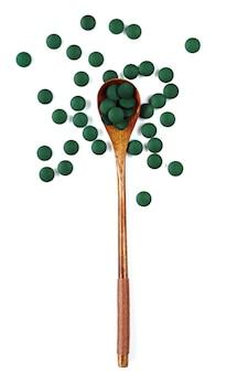 Droge spirulina in tabletten in een houten lepel op een geïsoleerd wit