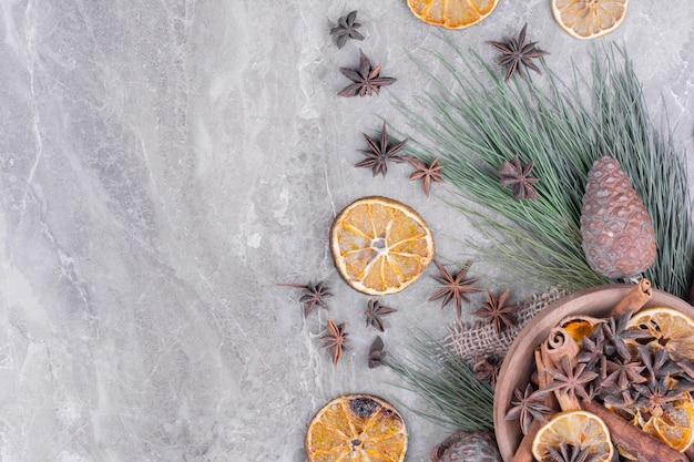 Droge stukjes sinaasappel met anijs in een houten beker.