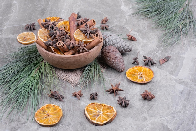 Droge stukjes sinaasappel, pijpjes kaneel en anijsbloemen in een houten kop