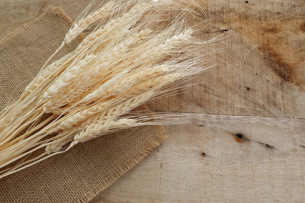 Droge tarwe en zakdoek op houten raad
