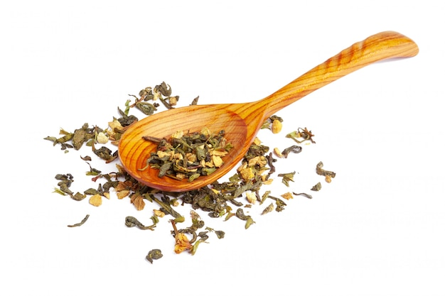 Droge thee op een houten lepel, die op wit wordt geïsoleerd