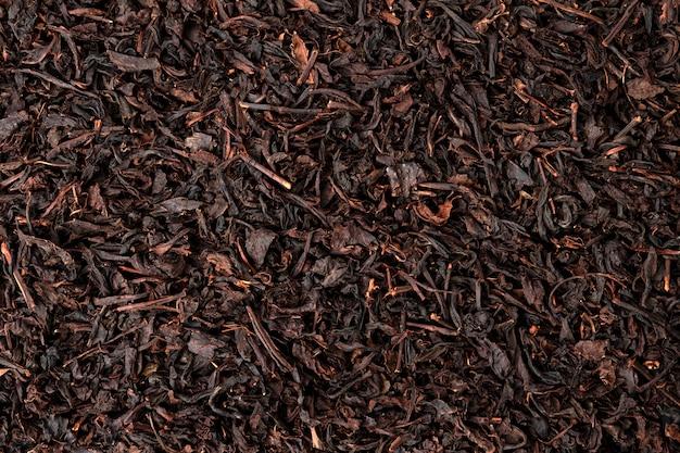 Droge theeblaadjesachtergrond of textuur, zwart theepatroon