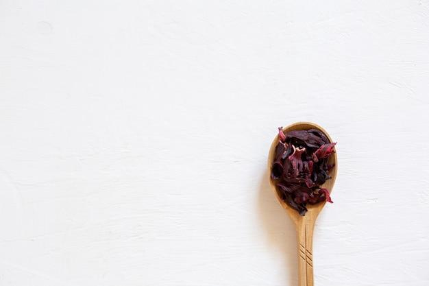 Droge theebladeren van rode hibiscus in een houten lepel