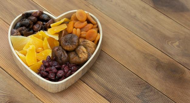 Droge vruchtenmengeling in de houten die doos van de hartvorm op houten achtergrond wordt geïsoleerd.