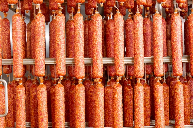 Droge worst opknoping op touw op metalen frame in het rookhuis