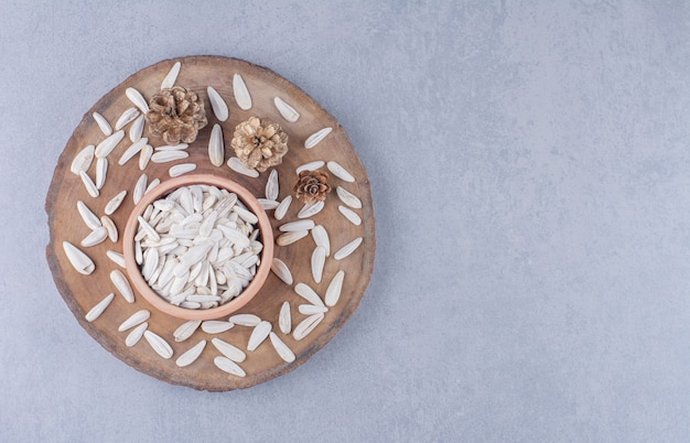Droge zonnebloempitten in kom op een bord op het marmeren oppervlak
