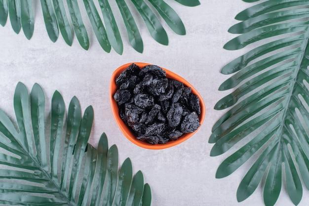 Droge zwarte pruimen in een voedselbeker op een betonnen ondergrond