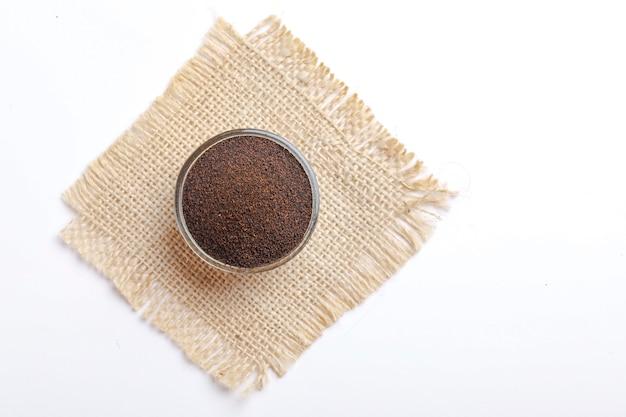 Droge zwarte thee in glazen kom op witte achtergrond