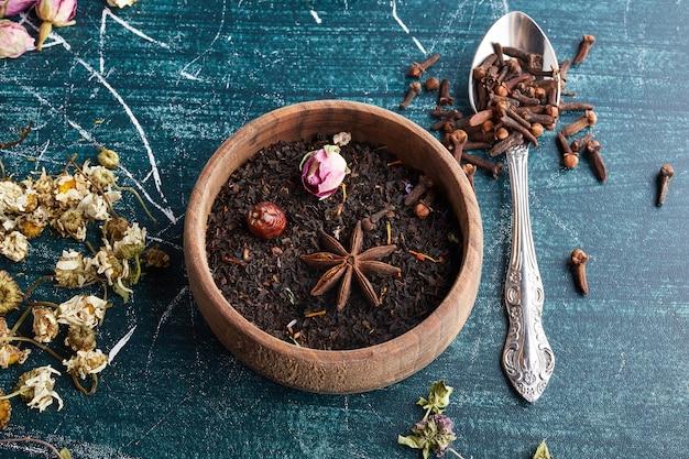 Droge zwarte theeblaadjes in een houten beker.