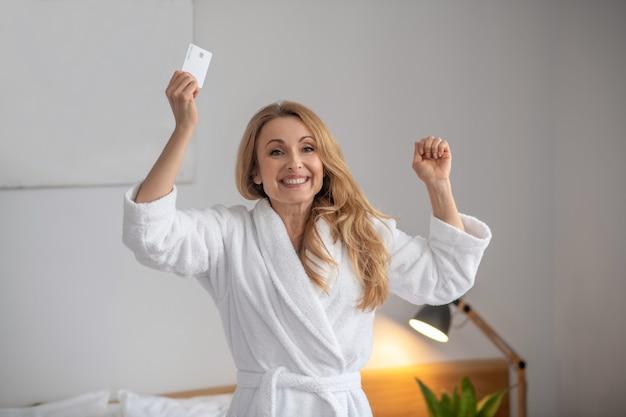 Dromen die uitkomen. gelukkig stralende volwassen vrouw in witte jas met creditcard in opgeheven hand in lichte kamer in goed humeur