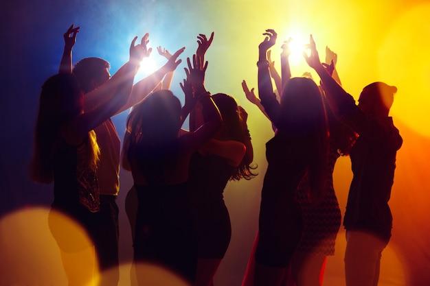 Dromen. een menigte van mensen in silhouet steekt hun handen op dansvloer op neonlichtachtergrond. nachtleven, club, muziek, dans, beweging, jeugd. geelblauwe kleuren en bewegende meisjes en jongens.