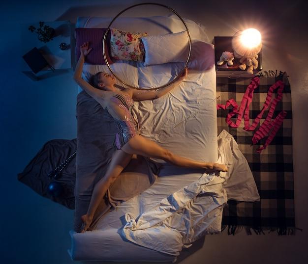 Dromen komen uit. bovenaanzicht van jonge professionele ritmische turnster slapen in de slaapkamer in sportkleding. houd meer van sport dan van comfort, kijk naar prestaties, zelfs in rust. actie, beweging, humor, thuis.