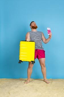 Dromen komen uit. gelukkig jonge man met tas voorbereid op reizen op blauwe studio achtergrond. concept van menselijke emoties, gezichtsuitdrukking, zomervakantie, weekend. zomer, zee, oceaan, alcohol.