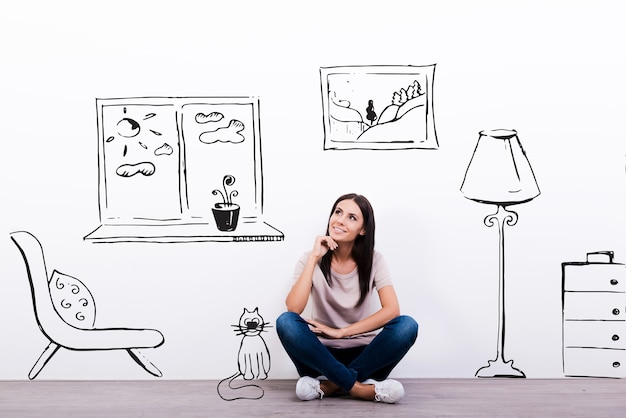 Dromen over een nieuw huis. nadenkende jonge vrouw die naar de schets op de muur kijkt