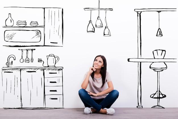 Dromen over nieuwe keuken. vrolijke jonge vrouw die lacht zittend op de vloer tegen een witte achtergrond met getekende keuken