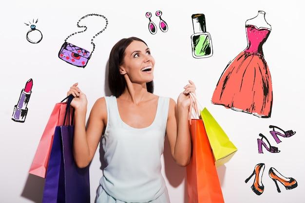 Dromen over nieuwe... opgewonden jonge vrouw in jurk die kleurrijke boodschappentassen draagt en omhoog kijkt