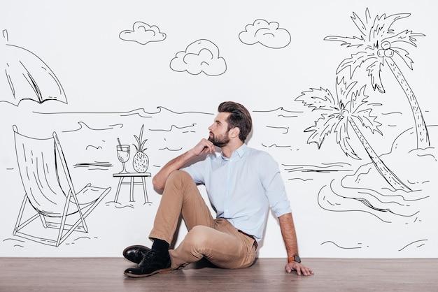 Dromen over vakantie. jonge knappe man die de hand op de kin houdt en wegkijkt terwijl hij op de vloer zit met een afbeelding van een resort op de achtergrond