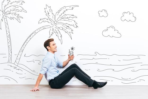 Dromen over vakantie. jonge knappe man die een getekende cocktail vasthoudt en wegkijkt met een glimlach terwijl hij op de vloer zit met een afbeelding van een resort op de achtergrond
