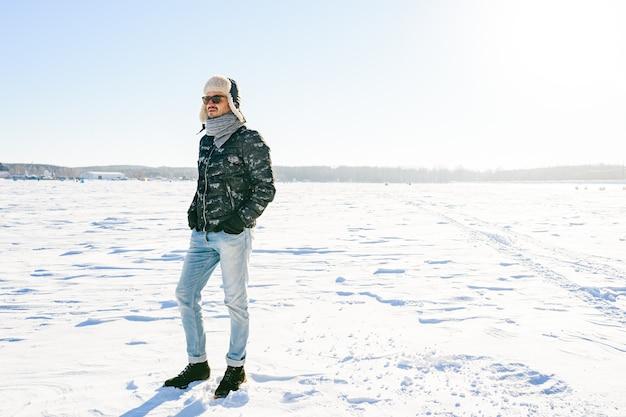 Dromen stijlvolle man in zonnebril poseren in het sneeuwveld