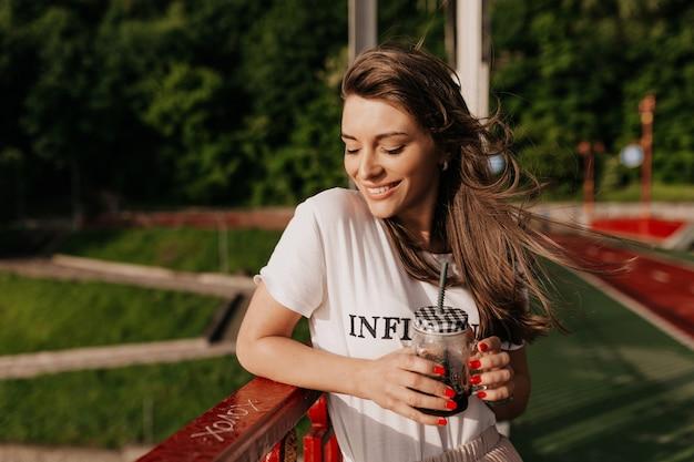 Dromen van gelukkige vrouw, gekleed in een wit t-shirt, drinken 's ochtends koffie en lopen op zonnige straat met een gelukkige glimlach
