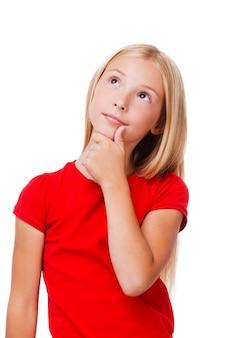 Dromen van... nadenkend meisje houdt hand op kin en kijkt weg terwijl ze geïsoleerd op wit staat